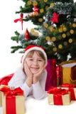 Girl in Santa hat lying under Christmas tree royalty free stock photo