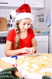 Girl in Santa hat makes cookies from dough Royalty Free Stock Photo