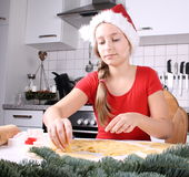 A girl in Santa hat makes cookies from dough Stock Image