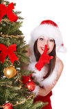 Girl in santa hat making silence gesture. Royalty Free Stock Photos
