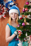 Girl in Santa hat near Christmas  fir-tree Royalty Free Stock Photo