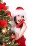 Girl in santa hat near  christmas tree. Royalty Free Stock Image