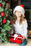 Girl in Santa hat near christmas tree Royalty Free Stock Photos