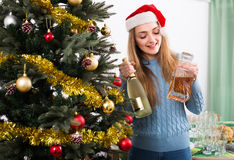 Girl in Santa hat near Christmas tree. Happy  smiling girl in Santa hat with champagne near Christmas tree Stock Photos