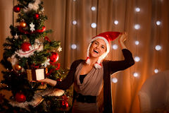 Girl in Santa hat near Christmas tree with present Stock Photography