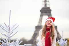 Girl in Santa hat near the Eiffel tower Royalty Free Stock Photo