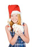 Girl in santa hat with pet rabbit Royalty Free Stock Image