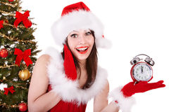 Girl in santa hat point on alarm clock . Stock Photos
