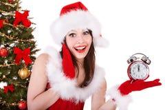 Girl in santa hat point on alarm clock . Girl in santa hat point on alarm clock by christmas tree. Isolated Stock Photos