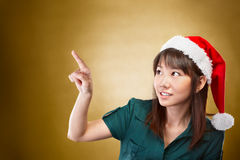 Girl with santa hat pointing away Royalty Free Stock Images
