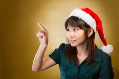 Girl with santa hat pointing away Royalty Free Stock Photo