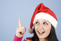 Girl with santa hat pointing up. To copy space and  looking very surprised and happy,check also  Christmas time,santa women and party time Stock Images