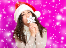 Girl in santa hat portrait with big snowflake toy posing on pink color background, christmas holiday concept, happy and emotions Stock Image