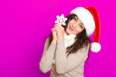 Girl in santa hat portrait with big snowflake toy posing on pink color background, christmas holiday concept, happy and emotions Royalty Free Stock Images