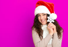 Girl in santa hat portrait with big snowflake toy posing on pink color background, christmas holiday concept, happy and emotions Stock Photo