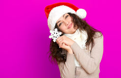 Girl in santa hat portrait with big snowflake toy posing on pink color background, christmas holiday concept, happy and emotions Stock Photography