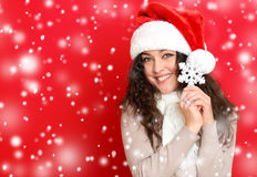 Girl in santa hat portrait with big snowflake toy posing on red color background, christmas holiday concept, happy and emotions stock photography
