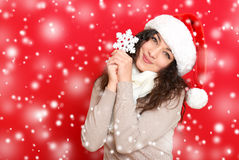 Girl in santa hat portrait with big snowflake toy posing on red color background, christmas holiday concept, happy and emotions Stock Image