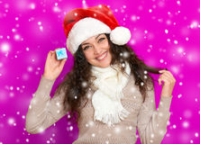 Girl in santa hat portrait with little gift box posing on pink color background, christmas holiday concept, happy and emotions Royalty Free Stock Images