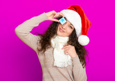 Girl in santa hat portrait with little gift box posing on pink color background, christmas holiday concept, happy and emotions Stock Photo