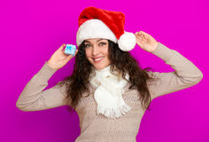 Girl in santa hat portrait with little gift box posing on pink color background, christmas holiday concept, happy and emotions Stock Photography