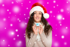 Girl in santa hat portrait with little gift box posing on pink color background, christmas holiday concept, happy and emotions Royalty Free Stock Photography