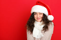 Girl in santa hat portrait on red color background, christmas holiday concept, happy and emotions Stock Photography