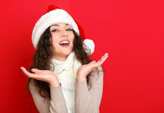 Girl in santa hat portrait on red color background, christmas holiday concept, happy and emotions Royalty Free Stock Photos