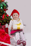 Girl in Santa hat with present on sledge Stock Photo