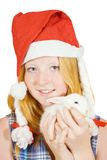 Girl  in santa hat with rabbit Stock Images