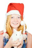 Girl in santa hat with rabbit Stock Photos