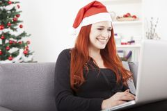 Girl with santa hat is shopping online Stock Image