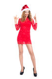 Girl in Santa hat showing sign of rock goat. Mischievous young woman in a red dress on a white background Stock Images