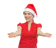 Girl in Santa hat showing something on empty palms Royalty Free Stock Photos