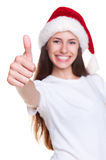 Girl in santa hat showing thumbs up Stock Photos
