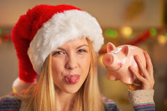Girl in santa hat showing tongue and piggy bank Stock Photography