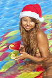Girl in Santa hat sitting in the swimming pool Royalty Free Stock Images