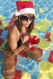 Girl in Santa hat sitting in the swimming pool Stock Images