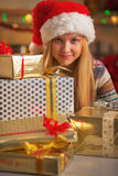 Girl in santa hat with stack of christmas present boxes Stock Image