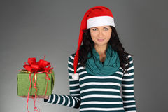 Girl in santa hat and striped dress with gift Royalty Free Stock Image