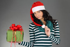 Girl in santa hat and striped dress with gift Royalty Free Stock Photos