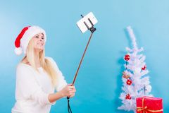 Girl in santa hat taking picture of herself using selfie stick Royalty Free Stock Images