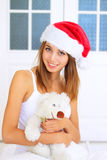 Girl in Santa hat with teddy bear Stock Image