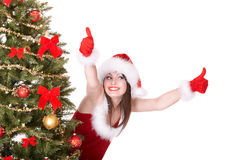 Girl in santa hat and tree with two thumb up Stock Photos