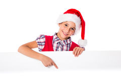 Girl in Santa hat with whiteboard. Happy girl in Santa hat pointing to blank whiteboard, isolated on white Stock Images