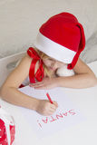 Girl in santa hat, writes a letter to Santa Stock Photo