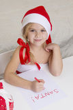 Girl in santa hat, writes a letter to Santa Royalty Free Stock Photography