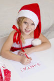 Girl in santa hat, writes a letter to Santa Royalty Free Stock Image