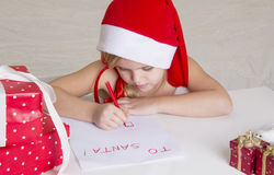 Girl in santa hat, writes a letter to Santa Stock Photos