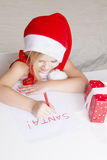 Girl in santa hat, writes a letter to Santa Royalty Free Stock Photos